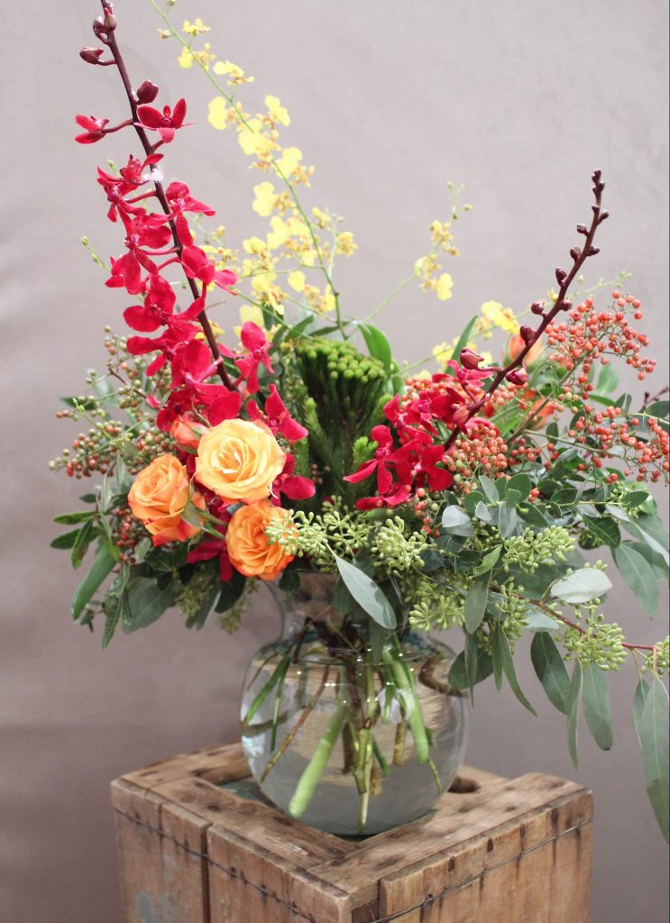 Bright red, yellow, and orange flowers mixed with greens in a glass bowl on a wooden crate.