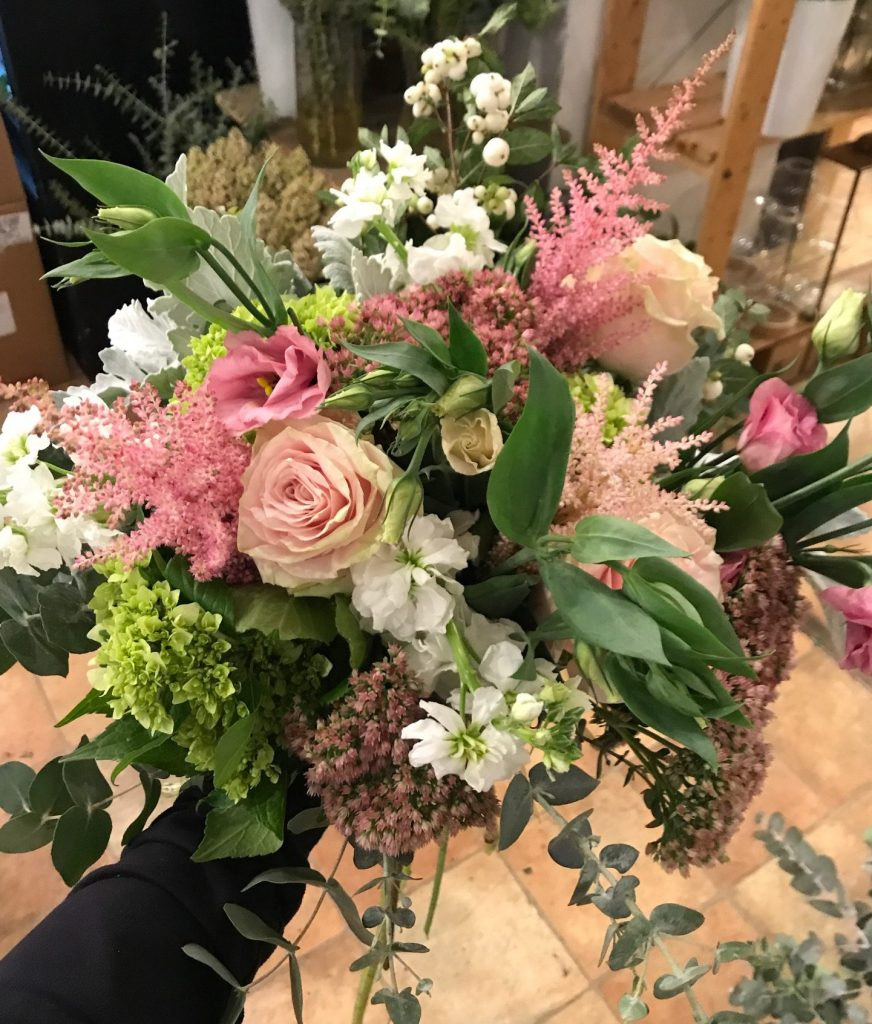 A floral bouquet of pale pinky-peach flowers with darker pink, white and rose coloured flowers mixed with greens.