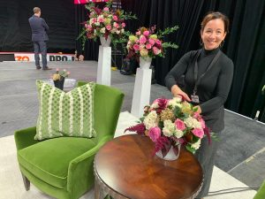 Elizabeth Young standing on stage beside floral arrangements for Michelle Obama