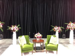 chairs on stage beside floral arrangements
