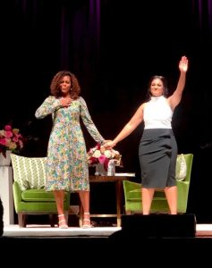 Komal Minhas and Michelle Obama on stage waving