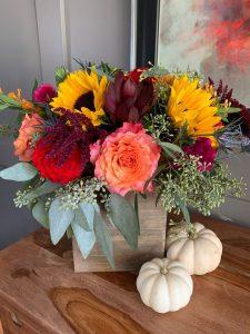 little pumpkins around arrangement and on table