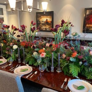 table centrepiece with Juliet garden roses, pincushion protea, red leucadendron, red ashima orchids, blue thistle red amaryllis, cedar, magnolia and dark burgundy scabiosa