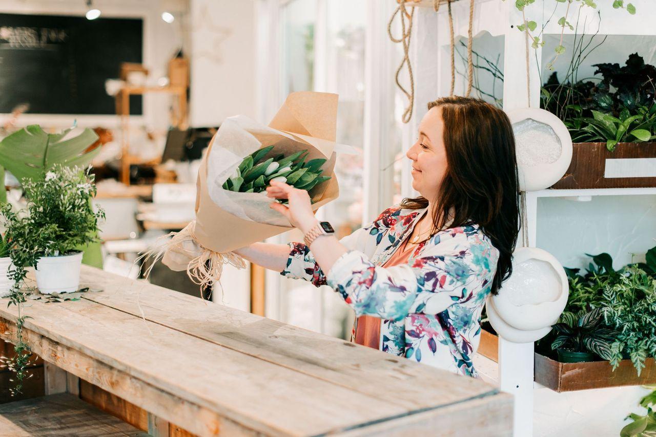 Elizabeth, owner of Flowers Talk Tivoli in Ottawa, is making a gift arrangement of flowers.